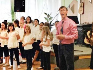 Раен Аинфелд, хормейстер в Саганаш начальной школе, и его группа детей выступают в центре Forever Young в Линкольнвуде. Фото: Ли Литас
